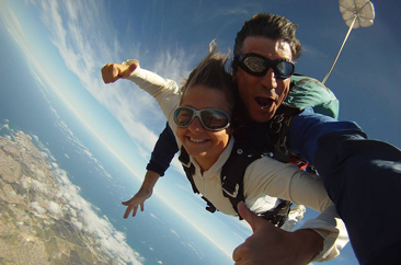 Tandem instructor and student smiling while skydiving in Mossel Bay, South Africa near Cape Town