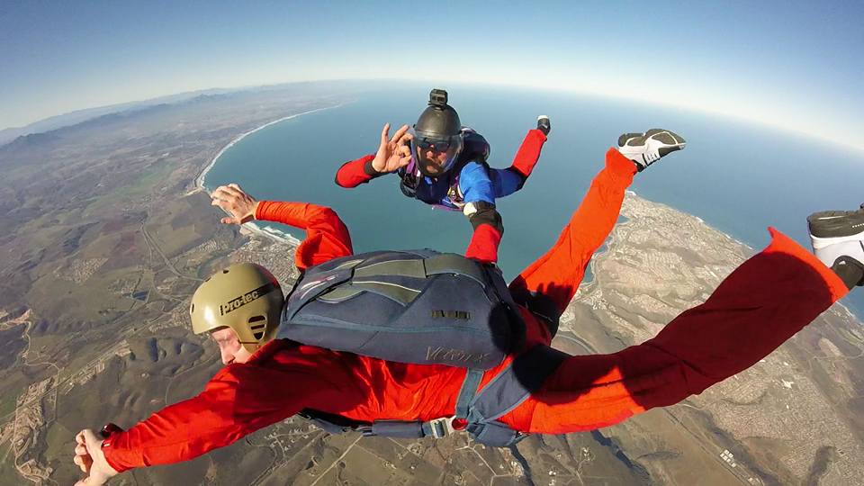 Two experienced skydivers wearing Red in free fall in Mossel Bay, South Africa
