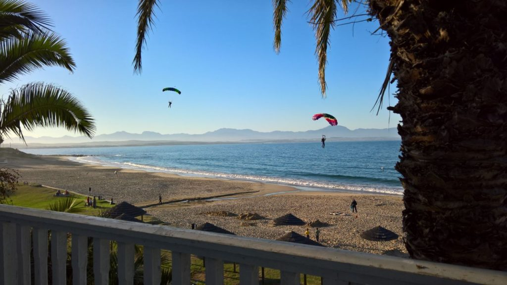 2 Skydivers under canopy getting ready to land on the beach in Garden Route, South Africa