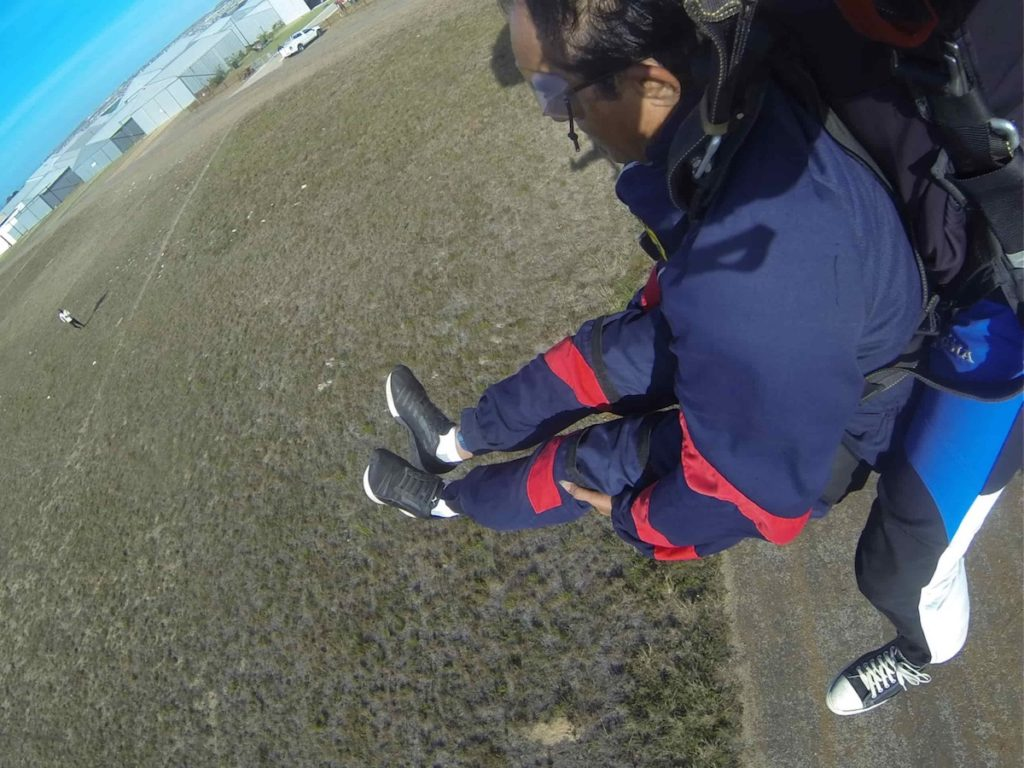 Tandem skydiver landing properly with knees and feet lifted