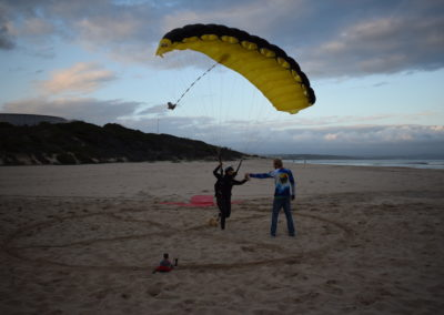 Skydiver with Yellow canopy landing on the beach in Garden Route, South Africa