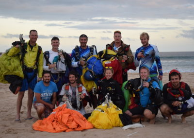 Group of 10 people celebrating on the beach post skydive in Mossel Bay, South Africa