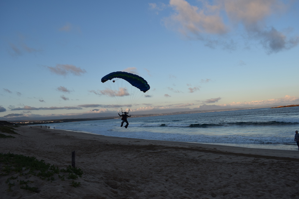 Person skydiving landing on the sand next to the ocean in Mossel Bay, South Africa