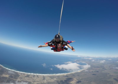 Instructor and student excited to be in free fall with blue ocean in the distance in South Africa, Mossel Bay