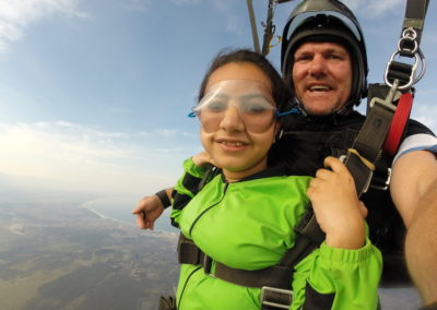 Skydiving student wearing green gear smiling while skydiving on Garden Route, South Africa