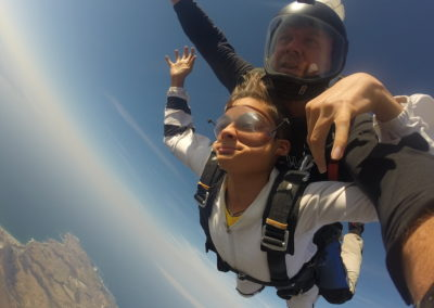 Instructor and Tandem student wearing white skydiving gear while skydiving in Mossel Bay, South Africa