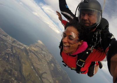 Female tandem skydiving in free fall with eyes closed is Mossel Bay, South Africa near Cape Town