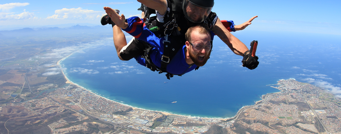 male tandem student stretching out arms in free fall while skydiving in Mossel Bay, South Africa