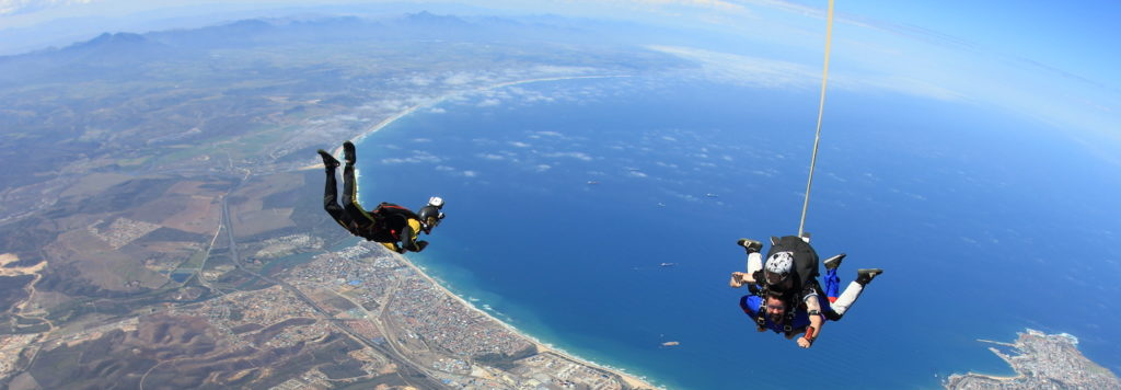 3 people in free fall over a bright blue ocean, skydiving over the Garden Route in Mossel Bay, South Africa