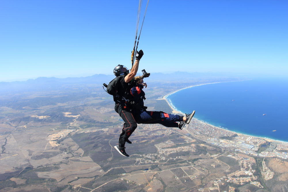 Tandem instructor and female student skydiving with bright blue oceans below the in Garden Route, South Africa