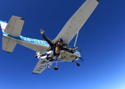 Female tandem student and instructor in free fall with white and blue plan in view while skydiving in Mossel Bay, South Africa