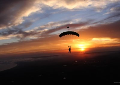 Tandem instructor and student under canopy with sunsetting in the distance in Mossel Bay South Africa