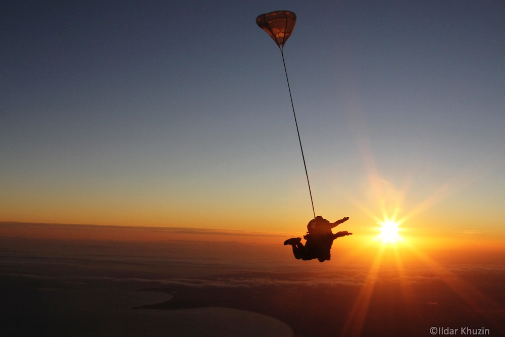 Tandem student and instructor skydiving in Mossel Bay, South Africa with sun in the distance