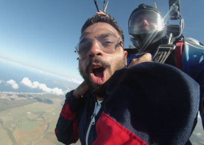 A man tandem skydiving for the first time