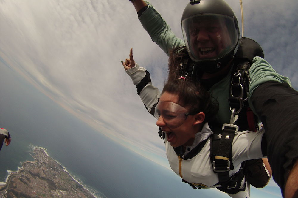 Woman taking a deep breath and giving a big yell while tandem skydiving