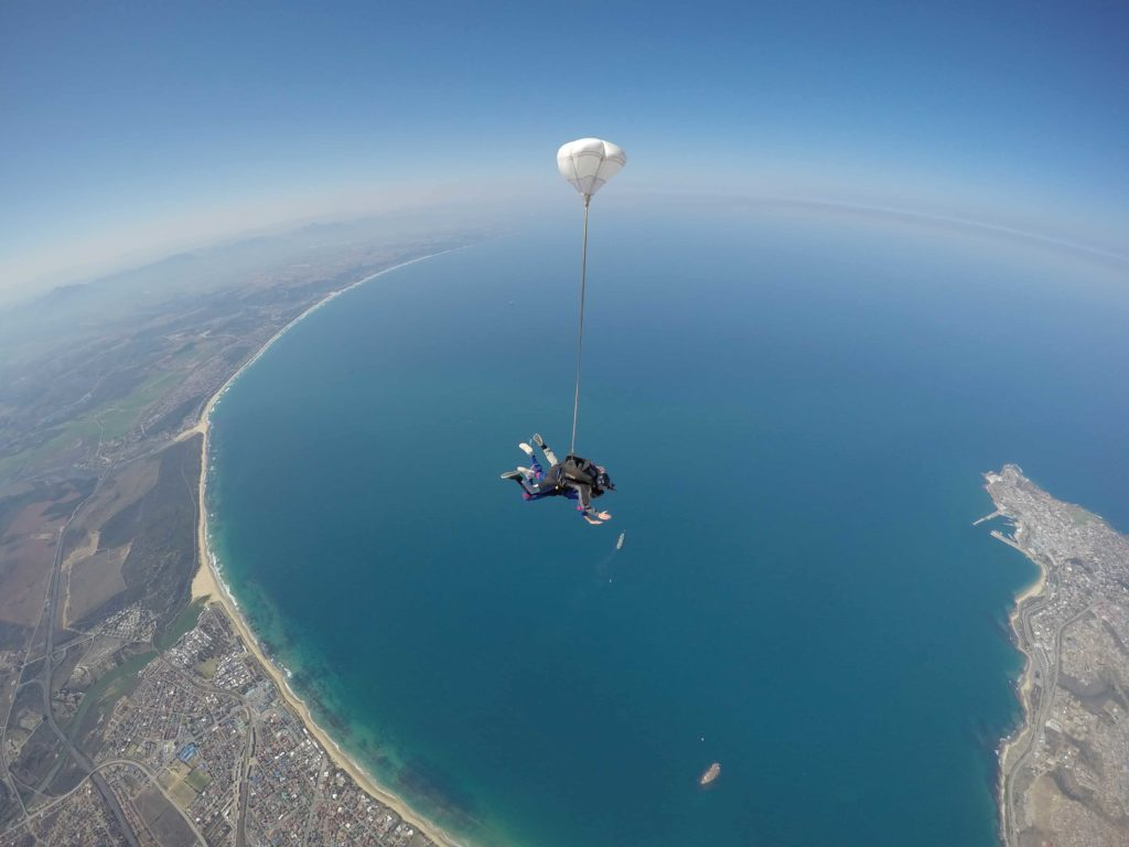 A parachute is deployed as a tandem skydiver takes in the view of Mossel Bay