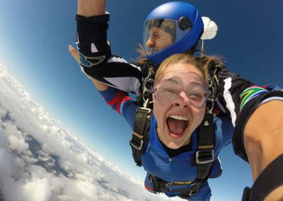 Girl having the time of her life as she is tandem skydiving over Mossel Bay near Cape Town