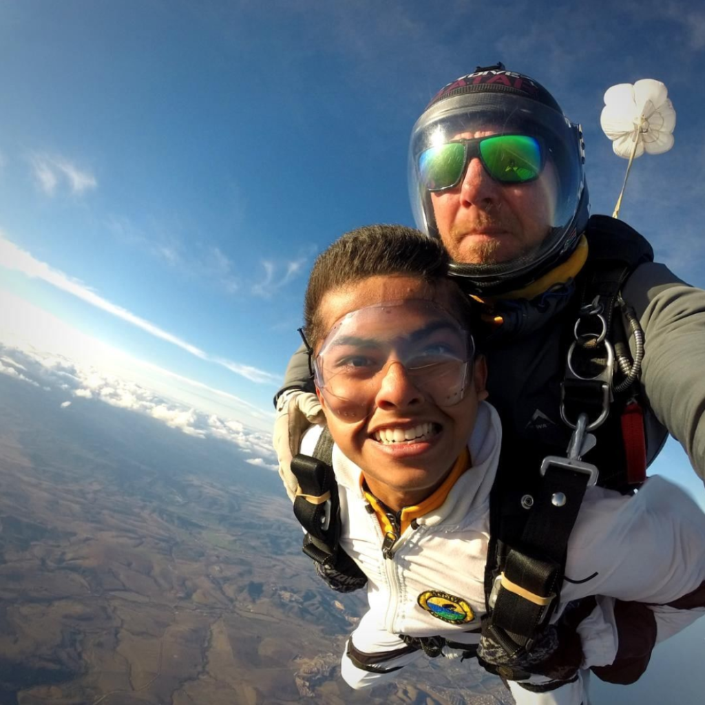 Man smiling as he enjoys the view while tandem skydiving over Mossel Bay, South Africa near Cape Town