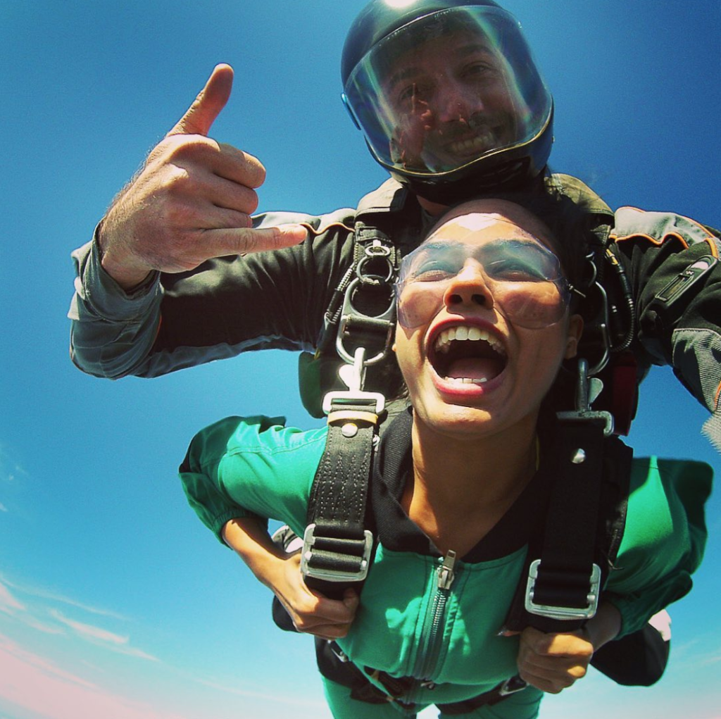 Woman screaming for joy as she sails through the air in a tandem skydive near Cape Town