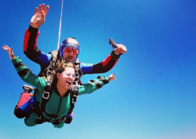 Woman screaming with joy as she finishes her first tandem skydive over Mossel Bay outside of Cape Town