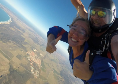 Woman tandem skydiving for the first time is loving the experience with Skydive Mossel Bay near Cape Town