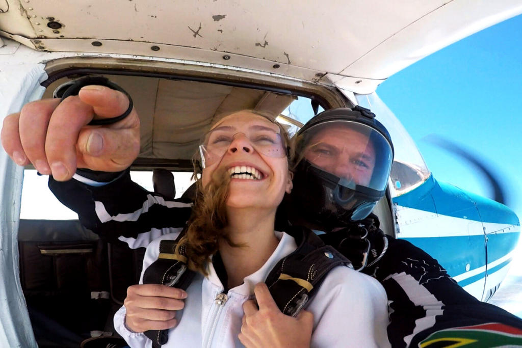Tandem skydivers excited about jumping into freefall over Mossel Bay, South Africa in the Western Cape
