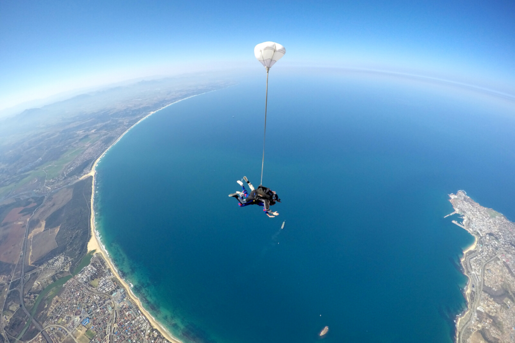 Tandem skydivers opening their parachute over Mossel Bay, South Africa