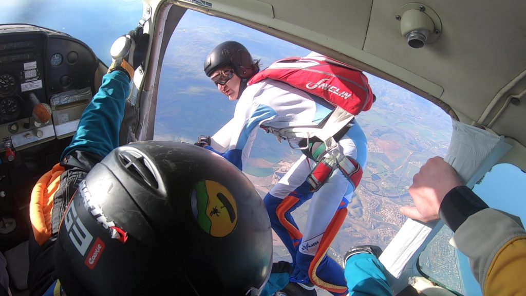 An experienced skydiver jumping from a plane over Mossel Bay near Cape Town