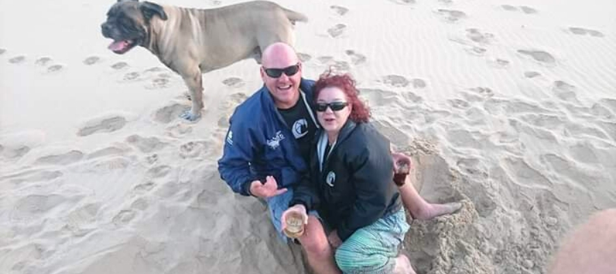 Corne smiles while posing with his wife on the beach in Mossel Bay, South Africa