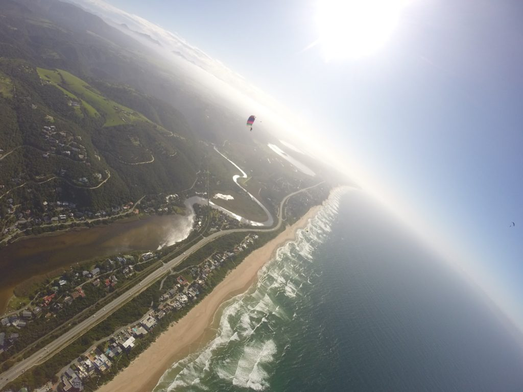 First-time skydiver jumping out of a plane over the beaches of Mossel Bay on the Garden Route near Cape Town