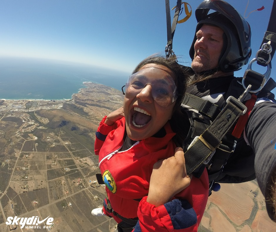 Woman tandem skydiving over Mossel Bay on the Garden Route near Cape Town