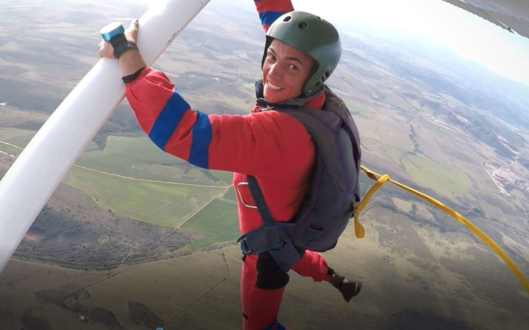 A static line student smiles while hanging from the strut of a plane at 3,500 feet at Skydive Mossel Bay near Cape Town South Africa